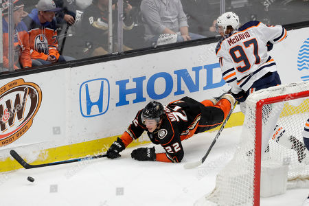 Edmonton Oilers center Connor McDavid, right, trips Anaheim Ducks left wing Sonny Milano during overtime in an NHL hockey game in Anaheim, Calif., . The Ducks won 4-3