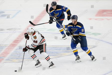Chicago Blackhawks' Patrick Kane (88) controls the puck while under pressure from St. Louis Blues' Oskar Sundqvist (70), of Sweden, and Tyler Bozak (21) during the third period of an NHL hockey game, in St. Louis