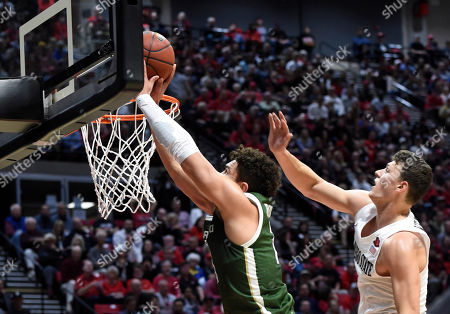 Colorado State guard David Roddy shoots past the defense of San Diego State forward Yanni Wetzell, right, during the first half of an NCAA college basketball game, in San Diego
