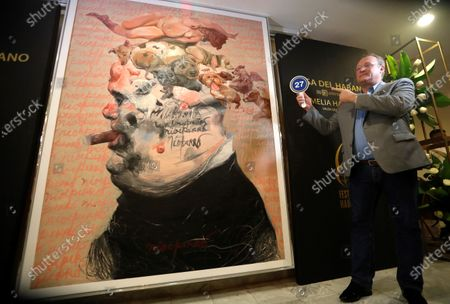 German Roland Henning poses for the photographers next to the artwork by Cuban artist Roberto Fabelo, priced at 170,000 US dollars (156,400 euros), after acquiring it at an auction within the Habanos Festival, at Melia Havana Hotel in Havana, Cuba, 26 February 2020. Roberto Fabelo will set the money to the Cuban health system.