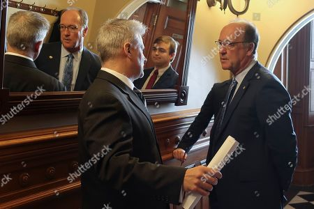 Tim Graham, left, a member of Kansas Gov. Laura Kelly's staff, confers with Senate Vice President Jeff Longbine, right, R-Emporia, outside the Senate chamber ahead of a debate on legalizing betting on sports events, at the Statehouse in Topeka, Kan. Pictured between them in the mirror is Michael Murray, Longbine's chief of staff
