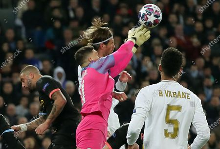 Real Madrid's Sergio Ramos (back) in action against Manchester City's goalkeeper Ederson Moraes (front) during the UEFA Champions League round of 16, first leg, soccer match between Real Madrid and Manchester City at Santiago Bernabeu stadium in Madrid, Spain, 26 February 2020.