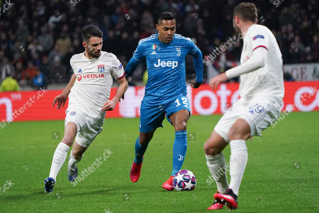 Juventus' Alex Sandro, center, Lyon's Leo Dubois, left, and Lyon's Lucas Tousart, right, vie for the ball during a round of sixteen, first leg, soccer match between Lyon and Juventus at the at the Lyon Olympic Stadium in Decines, outside Lyon, France