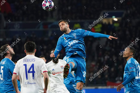 Juventus' Miralem Pjanic, left, and Juventus' Alex Sandro, watch as teammate Rodrigo Bentancur jumps top head the ball during a round of sixteen, first leg, soccer match between Lyon and Juventus at the at the Lyon Olympic Stadium in Decines, outside Lyon, France