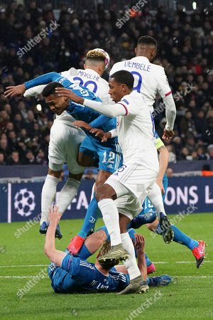 Juventus' Matthijs de Ligt, bottom, Juventus' Alex Sandro, center, and Lyon's Marcelo, right, vie for the ball during a round of sixteen, first leg, soccer match between Lyon and Juventus at the at the Lyon Olympic Stadium in Decines, outside Lyon, France