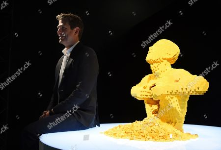 """Contemporary artist Nathan Sawaya sits next to his most well-known LEGO artwork """"Yellow,"""" at a media preview of """"The Art of the Brick"""" exhibition at the California Science Center, in Los Angeles. The exhibit, which features more than 100 works of art created from over one million LEGO bricks by Sawaya, opens on February 28"""