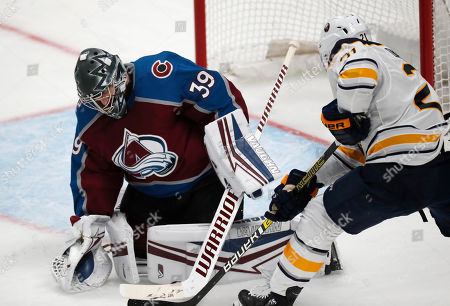 Colorado Avalanche goaltender Pavel Francouz, left, makes a pad save against Buffalo Sabres right wing Kyle Okposo during the third period of an NHL hockey game, in Denver. The Avalanche won 3-2