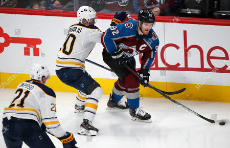 Colorado Avalanche left wing Gabriel Landeskog, right, passes the puck as Buffalo Sabres right wing Kyle Okposo, front left, and defenseman Henri Jokiharju cover during the third period of an NHL hockey game, in Denver. The Avalanche won 3-2