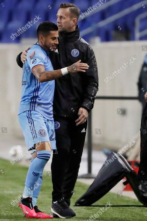 New York City FC head coach Ronny Deila, right, embraces defender Ronald Matarrita (22) after substituting for Mataritta during the second half in the second leg of a CONCACAF Champions League round of 16 soccer match against San Carlos, in Harrison, N.J. NYCFC defeated San Carlos 1-0