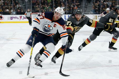 Edmonton Oilers center Connor McDavid (97) skates around Vegas Golden Knights defenseman Shea Theodore (27) during the first period of an NHL hockey game, in Las Vegas