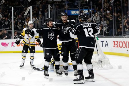 Los Angeles Kings' Trevor Lewis, center, celebrates his goal with Blake Lizotte, left, and Trevor Moore (12) during the second period of an NHL hockey game against the Pittsburgh Penguins, in Los Angeles