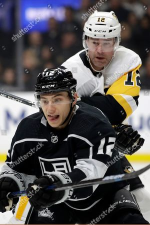 Los Angeles Kings center Trevor Moore, bottom, works under Pittsburgh Penguins' Patrick Marleau during the first period of an NHL hockey game, in Los Angeles