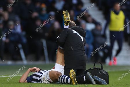 Ahmed Hegazi of West Bromwich Albion lies on the pitch as he receives treatment