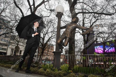 Stock Photo of The joyful and iconic figure of Gene Kelly on a lamppost from the timeless dance sequence he directed and choreographed for 'Singin' in the Rain' (1952) was revealed by a dance troupe from London's Bird College, reliving the timeless dance sequence.