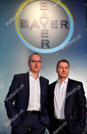 CEO Werner Baumann and CFO Wolfgang Nickl of Bayer AG, from left, stand under the logo at the Financial News Conference in Leverkusen, Germany, . The German drug and chemical company announced increased sales of 43.545 billion euros and a net income of 4.091 euros for 2019. Bayer is still facing major legal battles over the Roundup weed killer after the acquisition of Monsanto in 2018