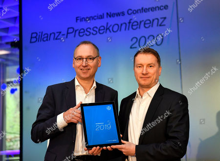 CEO Werner Baumann and CFO Wolfgang Nickl of Bayer AG, from left, holding the results at the Financial News Conference in Leverkusen, Germany, . The German drug and chemical company announced increased sales of 43.545 billion euros and a net income of 4.091 euros for 2019. Bayer is still facing major legal battles over the Roundup weed killer after the acquisition of Monsanto in 2018
