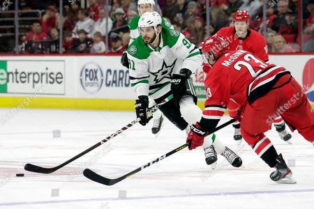 Tyler Seguin, Brock McGinn. Dallas Stars' Tyler Seguin (91) and Carolina Hurricanes' Brock McGinn (23) go for the puck during the first period of an NHL hockey game in Raleigh, N.C., on