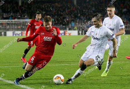 Alkmaar's Fredrik Midtsjo, left, challenge for the ball with LASK's James Holland during the Europa League round of 32, second leg, soccer match between LASK and AZ Alkmaar at the Linz Stadium in Linz, Austria