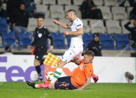 Sporting's Andraz Sporar, top, tries to dribble past Basaksehir's Martin Skrtel, during their Europa League Group Round of 32 second leg soccer match between Basaksehir and Sporting Lisbon, in Istanbul