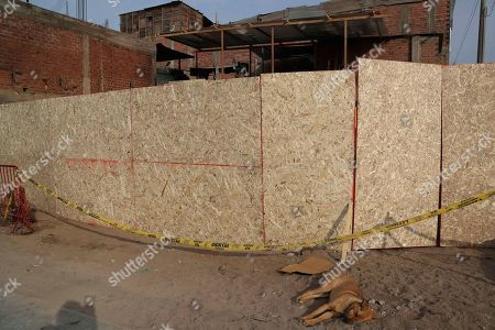"""Stock Picture of This photo shows a makeshift fence made from particle board surround a home that was destroyed a month ago when a gas tanker leak triggered fires and explosions killing 30 people, in the Sector 6 neighborhood of the Villa El Salvador district of Lima, Peru. """"Nobody has been jailed. There's no justice,"""" said 26-year-old Vanesa Meza, who lost her aunt and four nieces in the disaster"""