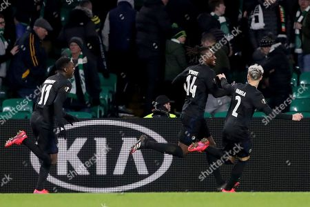 Copenhagen's Dame N'Doye, center, celebrates with Copenhagen's Guillermo Varela, right, after scoring his side's third goal during the Europa League round of 32, second leg soccer match between Celtic and FC Copenhagen at the Celtic Park stadium in Glasgow, Scotland