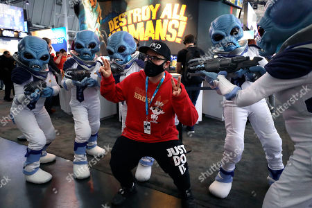 "Eric Vita, of Morris Plains, N.J., center, wears a protective mask while posing for a photograph with people dressed as ""Crypto,"" the main character in the video game ""Destroy All Humans!,"", at the Pax East conference, in Boston. Vita said concerns about the coronavirus played a role in his decision to wear a mask to the conference"