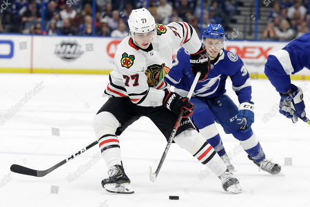 Chicago Blackhawks center Kirby Dach (77) moves the puck around Tampa Bay Lightning center Yanni Gourde (37) during the first period of an NHL hockey game, in Tampa, Fla
