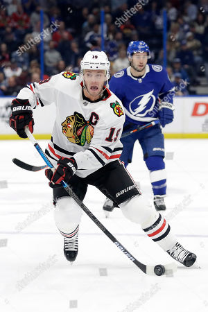 Chicago Blackhawks center Jonathan Toews (19) carries the puck after getting around Tampa Bay Lightning center Tyler Johnson (9) during the first period of an NHL hockey game, in Tampa, Fla