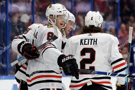 Chicago Blackhawks left wing Dominik Kubalik (8) celebrates his goal against the Tampa Bay Lightning with defenseman Duncan Keith (2) and center Jonathan Toews (19) during the third period of an NHL hockey game, in Tampa, Fla