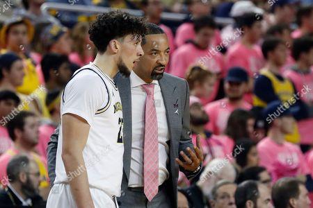 Michigan head coach Juwan Howard talks with forward Brandon Johns Jr. during the first half of an NCAA college basketball game, in Ann Arbor, Mich