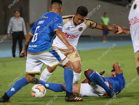 Stock Picture of Ivan Ledezma (R) and Diego Torres (L) of Audax Italiano vies for the ball with Miguel Carranza (C) of Cusco FC during a Copa Sudamericana soccer match between Audax Italiano and Cusco FC at Nacional stadium in Santiago, Chile, 27 February 2020.