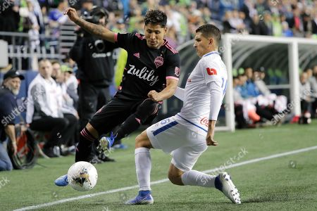 Seattle Sounders forward Raul Ruidiaz, left, tries to keep the ball in play as Olimpia defender Johnny Leveron, right, closes in during the first half of a CONCACAF Champions League soccer match, in Seattle