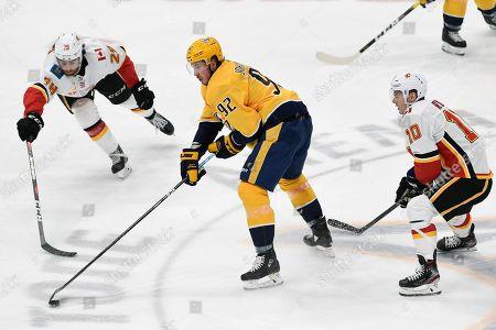 NAMES. Nashville Predators center Ryan Johansen (92) passes the puck between Calgary Flames' Dillon Dube (29) and Derek Ryan (10) during third period of an NHL hockey game, in Nashville, Tenn. The Predators won in overtime 4-3