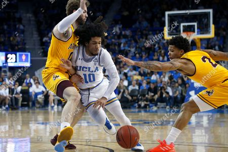 UCLA guard Tyger Campbell (10) drives between Arizona State forward Mickey Mitchell, left, and guard Rob Edwards (2) during an NCAA college basketball game, in Los Angeles