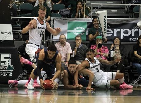 A large scramble involving Cal State Fullerton Titans forward Jackson Rowe (34), Cal State Fullerton Titans forward Johnny Wang (33), Hawaii Rainbow Warriors guard Eddie Stansberry (3), Hawaii Rainbow Warriors center Dawson Carper (44) and Hawaii Rainbow Warriors forward Zigmars Raimo (14) during a game between the Hawaii Rainbow Warriors and the Cal State Fullerton Titans at the Stan Sheriff Center in Honolulu, HI - Michael Sullivan/CSM