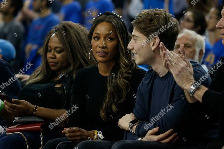 Cari Champion, center, attends an NCAA college basketball game between UCLA and Arizona State, in Los Angeles