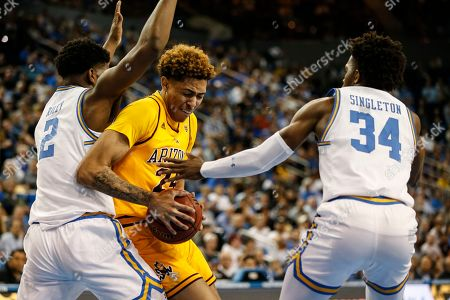 Arizona State forward Jalen Graham (24) drives between UCLA forward Cody Riley (2) and UCLA guard David Singleton (34) during an NCAA college basketball game, in Los Angeles