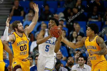 UCLA guard Chris Smith (5) is defended by Arizona State forward Mickey Mitchell (00) and Arizona State guard Rob Edwards (2) during an NCAA college basketball game, in Los Angeles