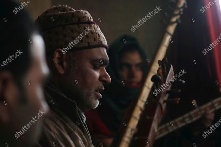Teacher Mohammad Yousuf (C) teaches the Kashmiri Muslim girls and boys to play instruments and sing Sufi music in Shilwat village, Bandipora district, Kashmir, India, 28 February 2020. Introduced in Kashmir in 15th century from Iran, Sufiana music, played with mystic poetry and Santoor, Rabab, Tabla and other musical instruments, is struggling for its survival in Kashmir.