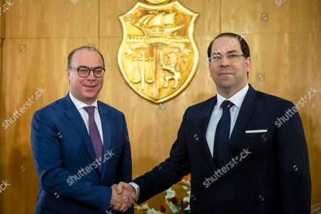Newly approved Tunisian Prime Minister Elyes Fakhfakh, left, shakes hand with outgoing Prime Minister Youssef Chahed during the hand over ceremony in Tunis, Friday, Feb.28, 2020. Tunisia has a new government at last, after four months of arguing among rival parties in the young North African democracy
