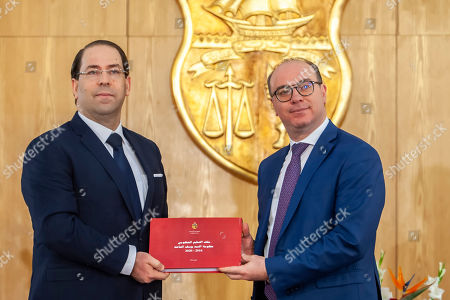 Newly approved Tunisian Prime Minister Elyes Fakhfakh, right, gets a document from outgoing Prime Minister Youssef Chahed during the hand over ceremony in Tunis, Friday, Feb.28, 2020. Tunisia has a new government at last, after four months of arguing among rival parties in the young North African democracy