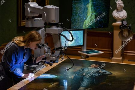 """John Chiang. In this file, photo, The Huntington Library, Art Museum, and Botanical Gardens senior paintings conservator Christina O'Connell, examines """"The Blue Boy"""" painting, made around 1770 by the English painter Thomas Gainsborough (1727-1788), through a Haag-Streit surgical microscope at """"Project Blue Boy"""" exhibit in the Thornton Portrait Gallery at the Huntington in San Marino, Calif. An 18-month restoration of the painting has been completed, and it will go back on display March 26, 2020, the institution said in a statement on Thursday, Feb. 27, 2020"""