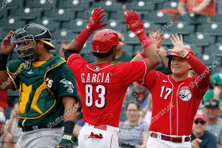 Stock Photo of Cincinnati Reds' Jose Garcia (83) celebrates his two-run home run with Josh VanMeter (17) as Oakland Athletics catcher Carlos Perez, left, adjusts his mask during the second inning of a spring training baseball game, in Goodyear, Ariz