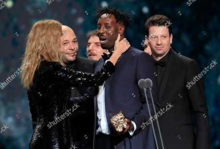 Sandrine Kiberlain, left, the President of the Cesar award ceremony congratulates director Ladj Ly for the Best Film with 'Les Miserables' on in Paris. The Cesar awards ceremony for France is the equivalent of the Oscars