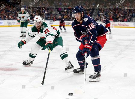 Stock Photo of Columbus Blue Jackets forward Alexander Wennberg, right, of Sweden, controls the puck in front of Minnesota Wild defenseman Greg Pateryn during the second period of an NHL hockey game in Columbus, Ohio