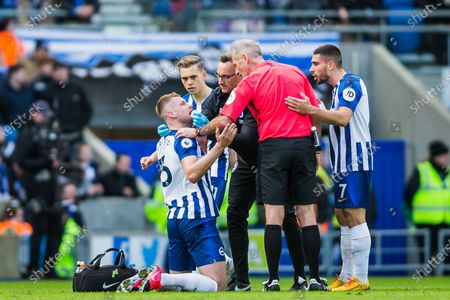 Martin Atkinson (Referee) talking with injured Adam Webster (Brighton) with Neal Maupay (Brighton) keen to talk to the ref too during the Premier League match between Brighton and Hove Albion and Crystal Palace at the American Express Community Stadium, Brighton and Hove