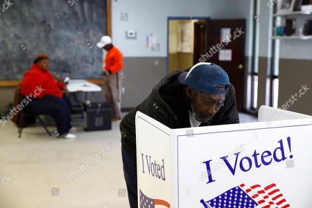 John Singleton fills out his ballot at a primary polling place, in Charleston, S.C