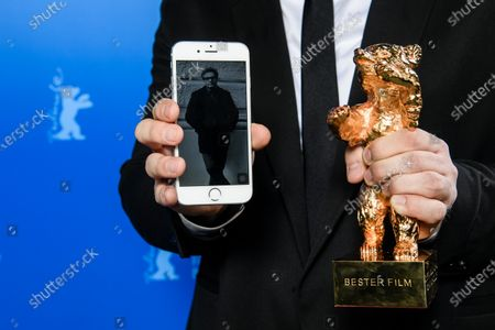 A member of the cast and crew of the awarded movie poses with the Golden Bear and a picture on a smartphone showing Iranian director Mohammad Rasoulof of the movie 'Sheytan vojud nadarad' (There Is No Evil) during the Closing and Awards Ceremony of the 70th annual Berlin International Film Festival (Berlinale), in Berlin, Germany, 29 February 2020. The Berlinale runs from 20 February to 01 March 2020.