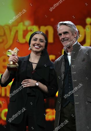 Baran Rasoulof, Jeremy Irons. Actress Baran Rasoulof, left, holds aloft The Golden Bear for Best Film in place of director Mohammad Rasoulof, who did not attend, for the film 'Sheytan vojud nadarad' (There Is No Evil), presented by actor Jeremy Irons during the award ceremony at the 70th International Berlinale Film Festival in Berlin, Germany