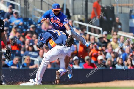 Houston Astros' Taylor Jones (79) and New York Mets third baseman Eduardo Nunez (12) collide as Nunez reaches for the throw on a triple by Jones during the second inning of a spring training baseball game, in West Palm Beach, Fla